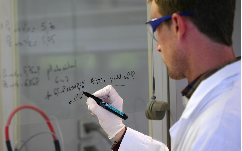 Un scientifique d'une trentaine d'années écrit une formule sur un tableau transparent avec un stylo noir.